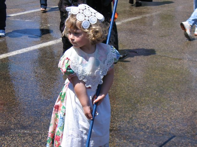 A cute little girl scrubbing the street.
