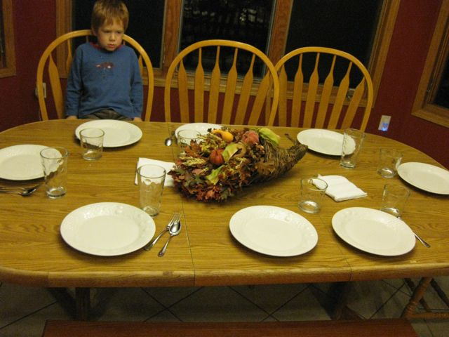 The table settings, with a hungry boy thinking that if he sits at the table supper will be done faster.